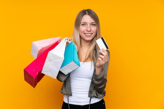 Jeune femme blonde sur jaune tenant des sacs à provisions et une carte de crédit