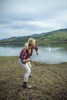 Jeune femme blonde jetant des pierres dans l'eau