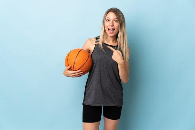 Jeune femme blonde jouant au basket-ball isolé sur le mur bleu, pointant le doigt sur le côté