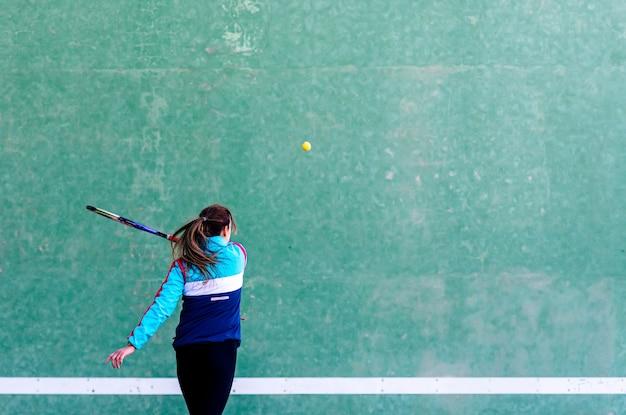 Jeune femme blonde jouant au racquetball ou au squash.