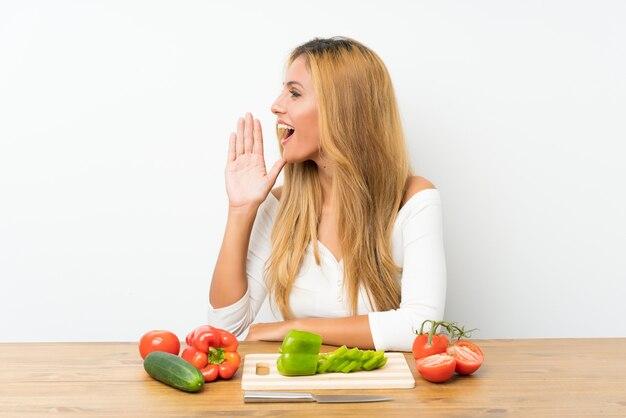 Jeune femme blonde avec des légumes dans une table en criant avec la bouche grande ouverte