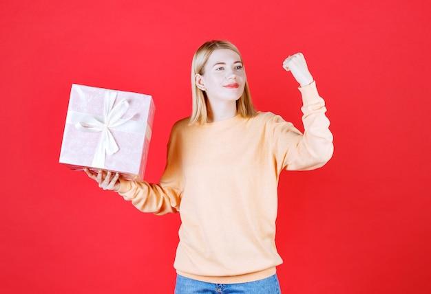 Jeune femme blonde levant le bras tout en tenant la boîte-cadeau devant le mur rouge