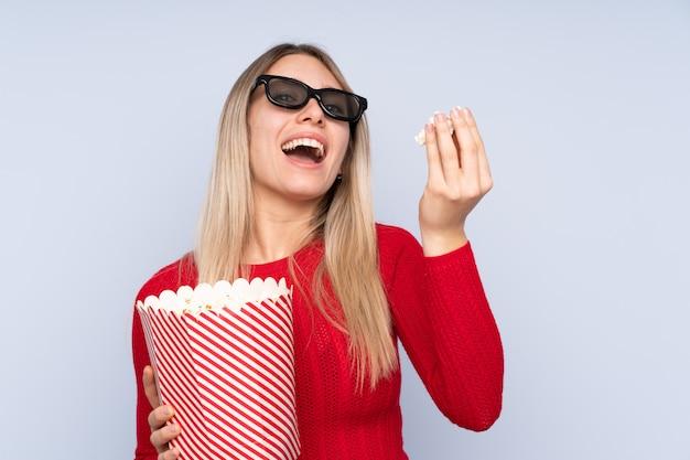 Jeune femme blonde avec des lunettes 3d et tenant un grand seau de pop-corn