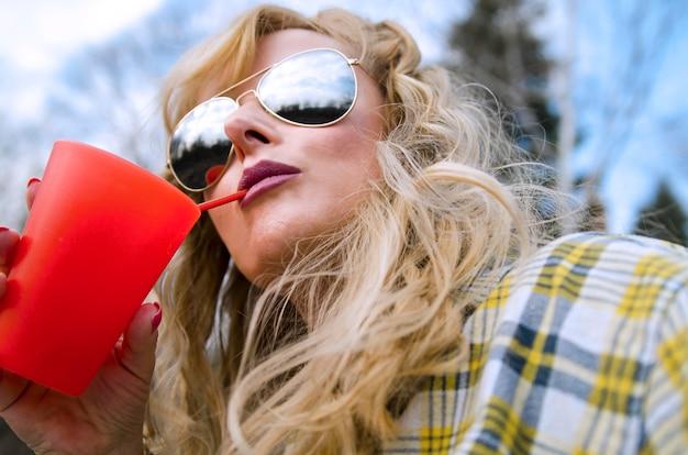 Jeune femme blonde avec des lunettes de soleil buvant sur la paille de verre rouge