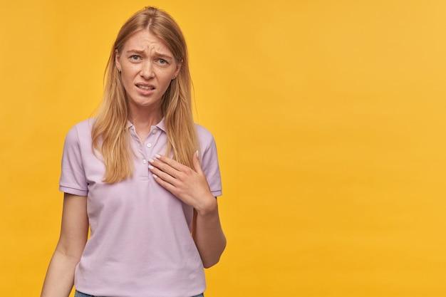 Une jeune femme blonde malheureuse et contrariée avec des taches de rousseur en t-shirt lavande se sent gênée et se montre du doigt par-dessus le mur jaune