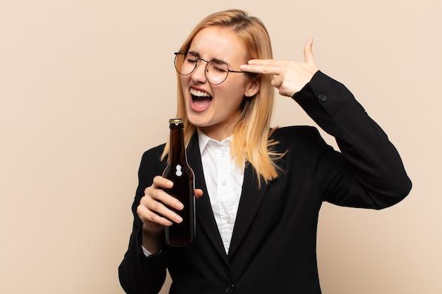 Jeune femme blonde à la malheureuse et stressée, geste de suicide faisant signe des armes à feu avec la main, pointant vers la tête