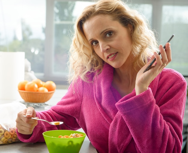 Jeune femme blonde mangeant des céréales le matin