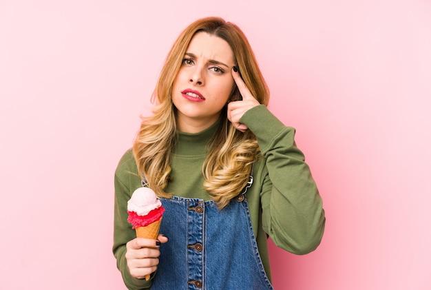 Jeune femme blonde mangeant une glace montrant un geste de déception avec l'index