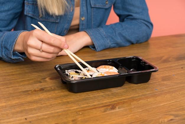 Jeune femme blonde mangeant des sushis