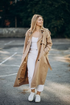 Jeune femme blonde en manteau beige marchant dans la rue