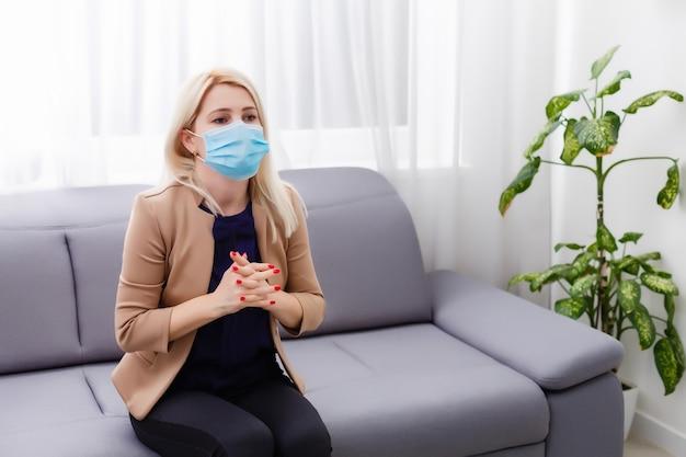 Une jeune femme blonde masquée s'inquiète de la quarantaine. coronavirus, maladie, infection, quarantaine, pansement chirurgical.