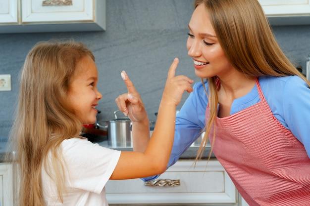 Jeune femme blonde, mère et ses enfants s'amusant pendant la cuisson de la pâte