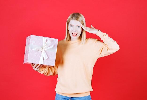 Jeune femme blonde met sa main près de son front tout en tenant la boîte-cadeau