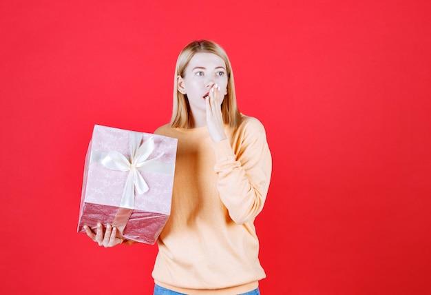 Jeune femme blonde met son doigt près de sa bouche devant le mur rouge