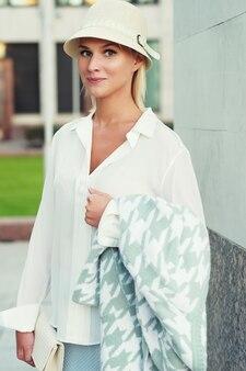 Jeune femme blonde de mode marchant dans la rue