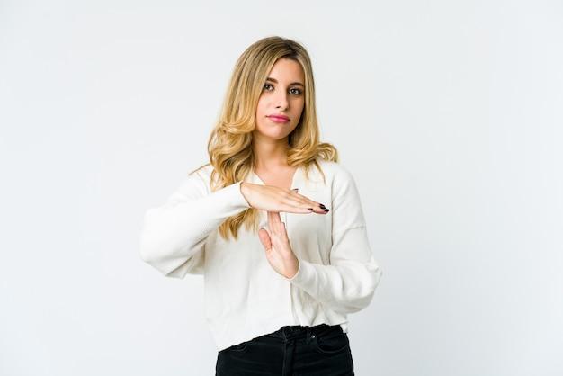 Jeune femme blonde montrant un geste de timeout