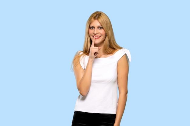 Jeune femme blonde montrant un signe de geste de silence sur fond bleu isolé