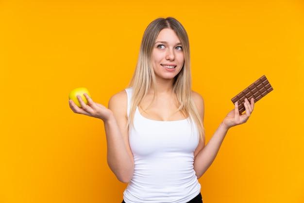 Jeune femme blonde sur mur bleu isolé ayant des doutes tout en prenant une tablette de chocolat dans une main et une pomme dans l'autre