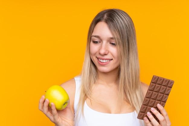 Jeune femme blonde sur un mur bleu isolé prenant une tablette de chocolat dans une main et une pomme dans l'autre
