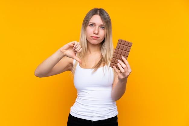 Jeune femme blonde sur un mur bleu isolé en prenant une tablette de chocolat faisant un mauvais signal