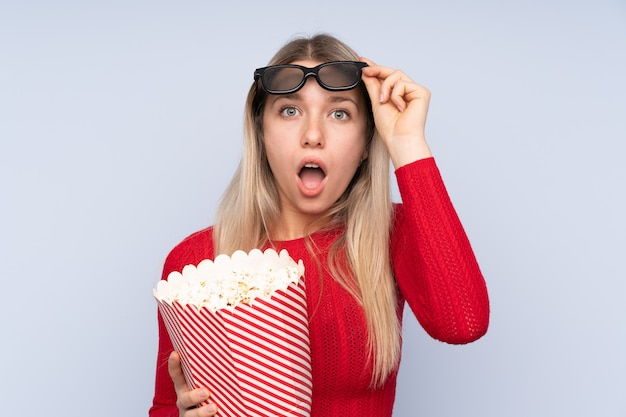 Jeune femme blonde sur mur bleu isolé surpris avec des lunettes 3d et tenant un grand seau de pop-corn