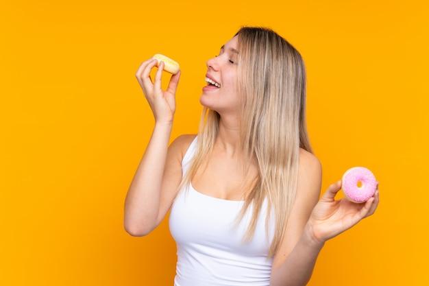 Jeune femme blonde sur un mur bleu isolé tenant des beignets avec une expression heureuse