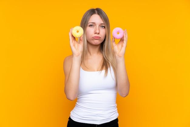Jeune femme blonde sur un mur bleu isolé tenant des beignets avec une expression triste