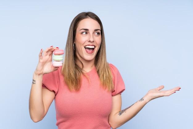 Jeune femme blonde sur un mur bleu isolé tenant des macarons français colorés avec une expression choquée