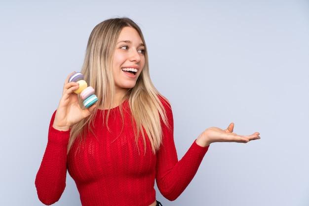 Jeune femme blonde sur un mur bleu isolé tenant des macarons français colorés et avec une expression surprise