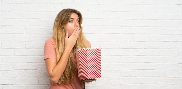 Jeune femme blonde sur le mur de briques blanches tenant un bol de pop-corn