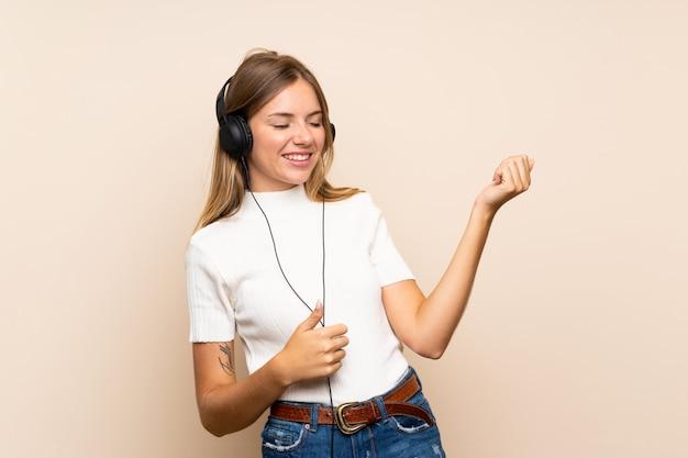 Jeune femme blonde sur un mur isolé à l'aide du téléphone portable avec casque et danse