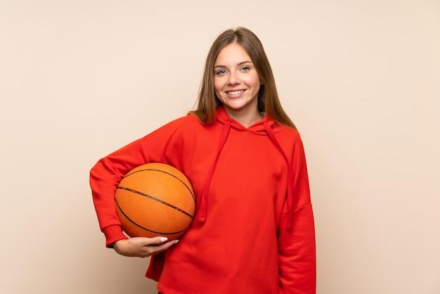 Jeune femme blonde sur un mur isolé avec ballon de basket