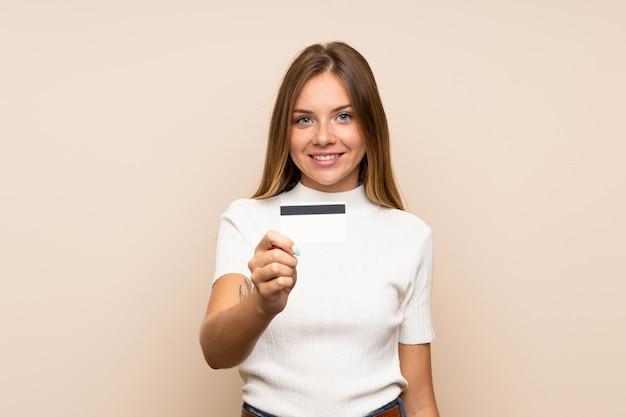 Jeune femme blonde sur mur isolé tenant une carte de crédit