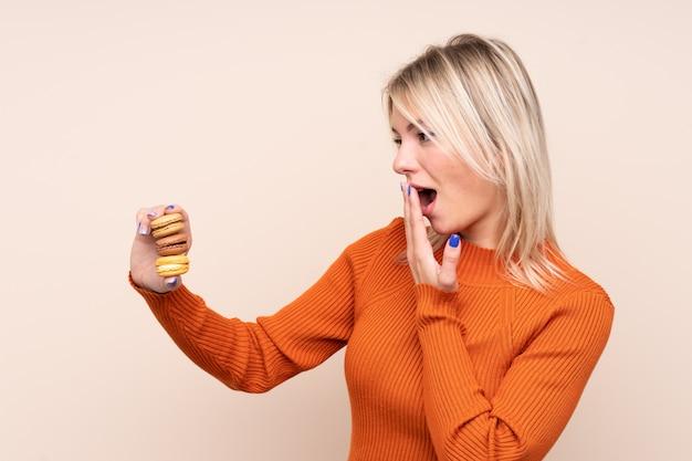 Jeune femme blonde sur un mur isolé tenant des macarons français colorés et avec une expression surprise