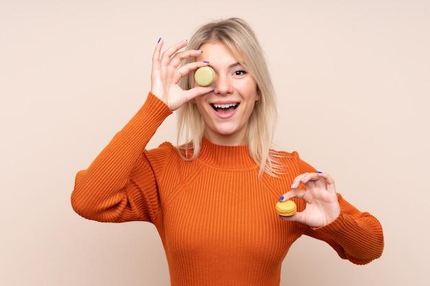 Jeune femme blonde sur un mur isolé tenant des macarons français colorés