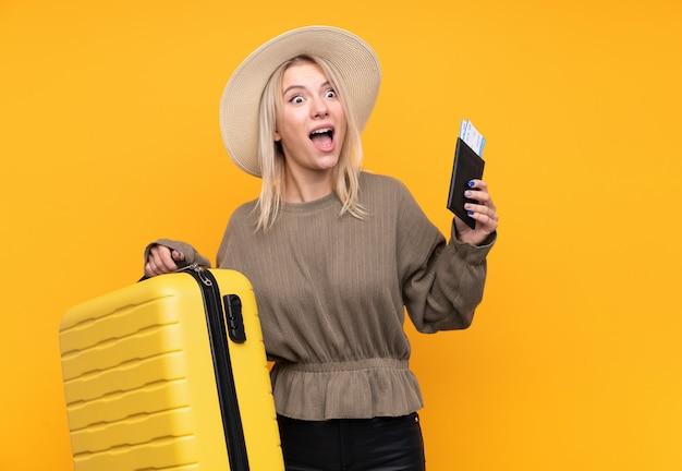 Jeune femme blonde sur mur jaune isolé en vacances avec valise et passeport et surpris