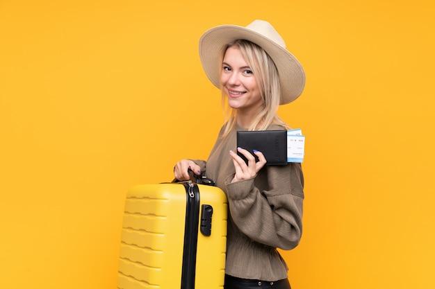 Jeune femme blonde sur un mur jaune isolé en vacances avec valise et passeport