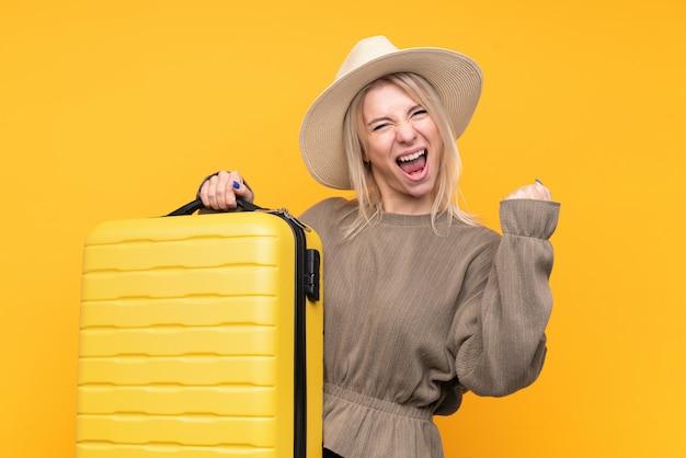 Jeune femme blonde sur mur jaune isolé en vacances avec valise de voyage et un chapeau