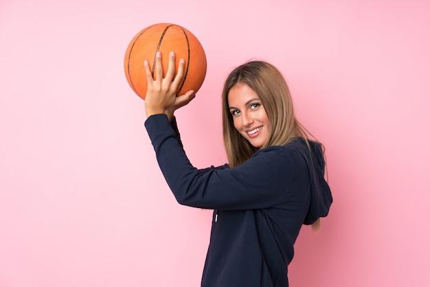 Jeune femme blonde sur un mur rose isolé avec ballon de basket