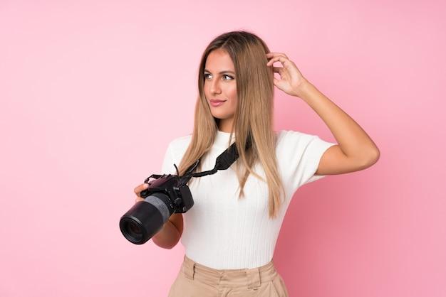 Jeune femme blonde sur un mur rose isolé avec une caméra professionnelle et pensant