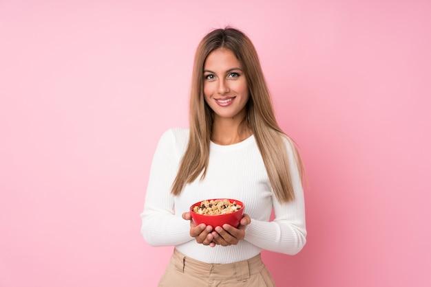 Jeune femme blonde sur un mur rose isolé, tenant un bol de céréales