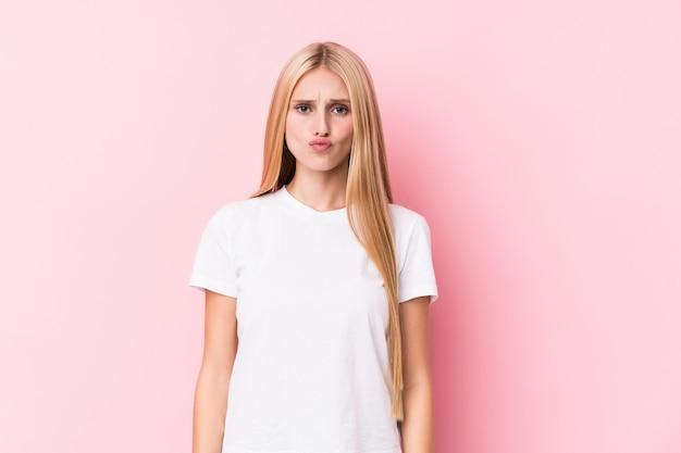 Jeune femme blonde sur un mur rose souffle les joues, a une expression fatiguée. concept d'expression faciale.