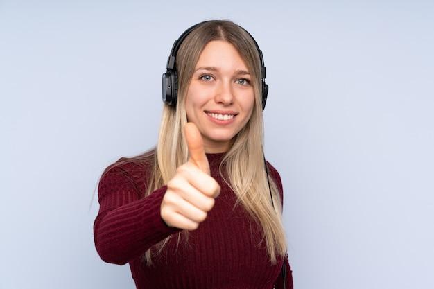 Jeune femme blonde sur la musique d'écoute bleue et avec le pouce vers le haut