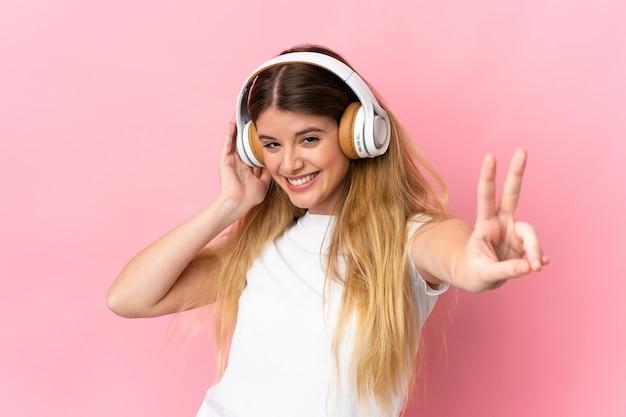 Jeune femme blonde sur musique d'écoute isolée avec un mobile et chant