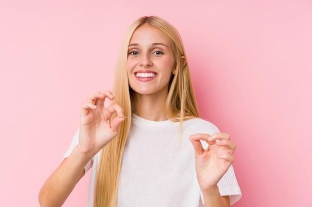 Jeune femme blonde, nettoyer ses dents avec un fil dentaire
