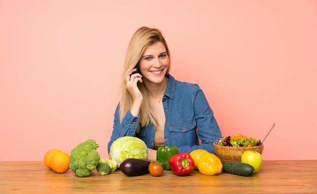 Jeune femme blonde avec de nombreux légumes en conversation avec le téléphone mobile