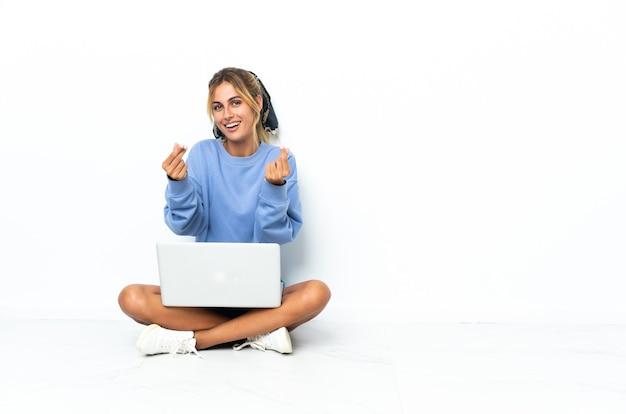 Jeune femme blonde avec l'ordinateur portable isolé faisant un geste d'argent