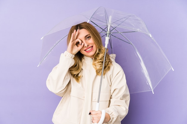 Jeune femme blonde avec un parapluie isolé jeune femme blonde avec un parapluie isolé excité en gardant le geste ok sur les yeux.