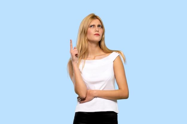 Jeune femme blonde pense à une idée, pointant le doigt vers le haut sur fond bleu isolé