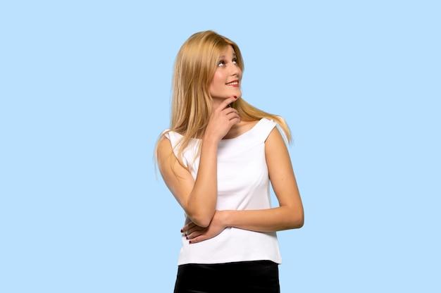 Jeune femme blonde pense à une idée tout en levant sur fond bleu isolé
